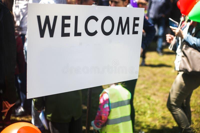 Biały znak powitalny w ulicie Zamazani ludzie odwiedza wydarzenie w mieście obraz royalty free