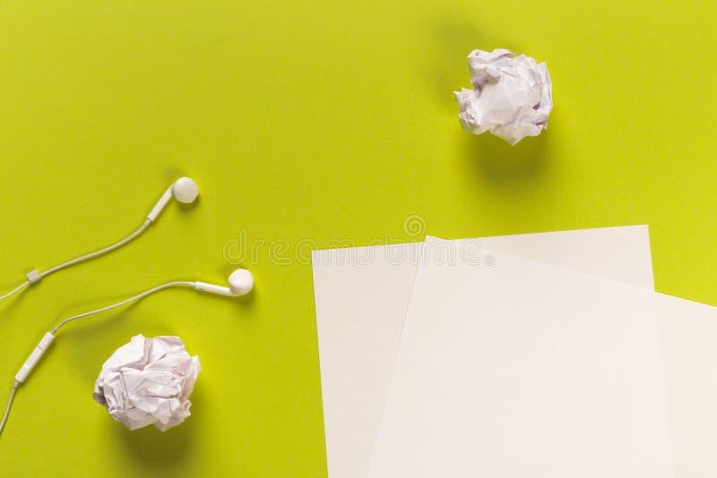 Białych księg prześcieradła na coloured backgroung z staczać się papierowymi i białymi słuchawkami fotografia royalty free