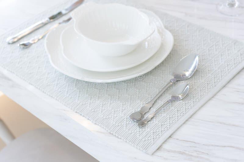 Białych kwiatów waza z nożem i rozwidlenie na bielu talerzu na rocznika drewnianym tle zdjęcie royalty free