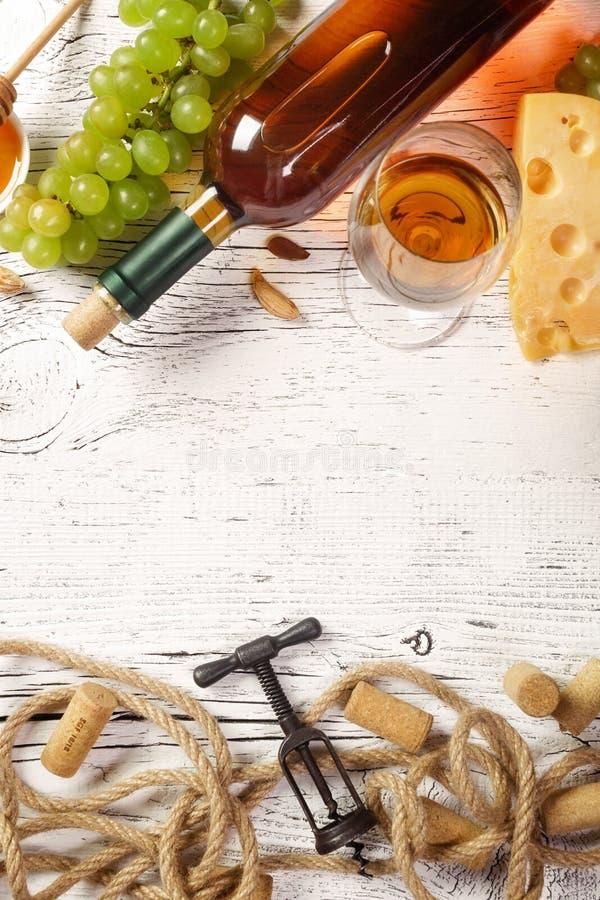 Bia?ego wina butelka, winogrono, mi?d, ser, wineglass z corkscrew, korki i arkana na bia?ej drewnianej desce, fotografia stock