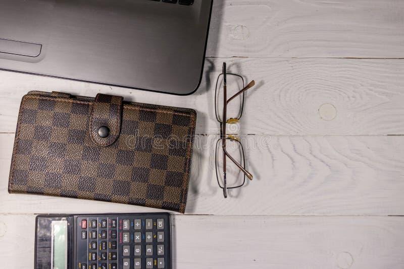 Bia?y biurowy biurko z laptopem, kalkulatorem, notepad, eyeglasses i pi?rem, Odg?rny widok, kopii przestrze? zdjęcia royalty free