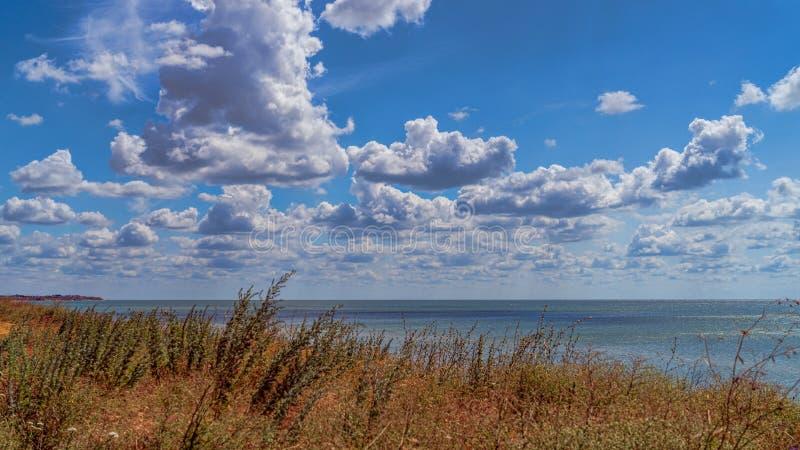Bia?y chmura p?awik przez niebieskie niebo zdjęcia stock