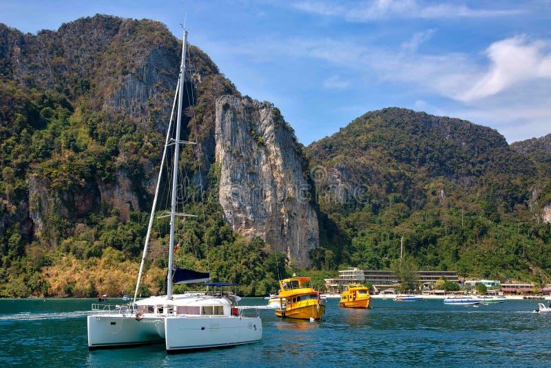 Bia?y ?eglowanie jacht w morzu Na tle Phi Phi wyspy linia brzegowa pasa?erskie motorowe ?odzie i obrazy royalty free
