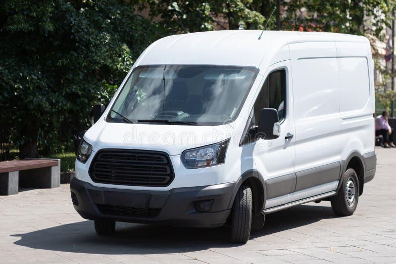 Bia?y minibus parkuje w miasto ulicie zdjęcia stock