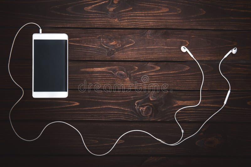Bia?y smartphone z he?mofonami na drewnianym t?o wizerunku muzyczny bawi? si? fotografia stock