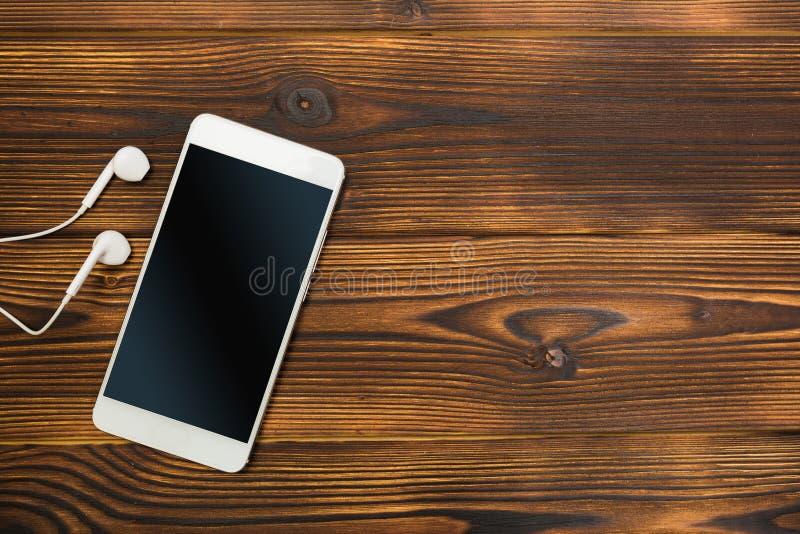 Bia?y smartphone z he?mofonami na drewnianym tle zdjęcie stock