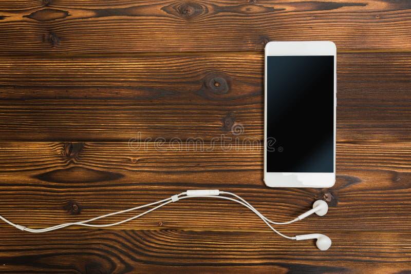 Bia?y smartphone z he?mofonami na drewnianym tle zdjęcie royalty free
