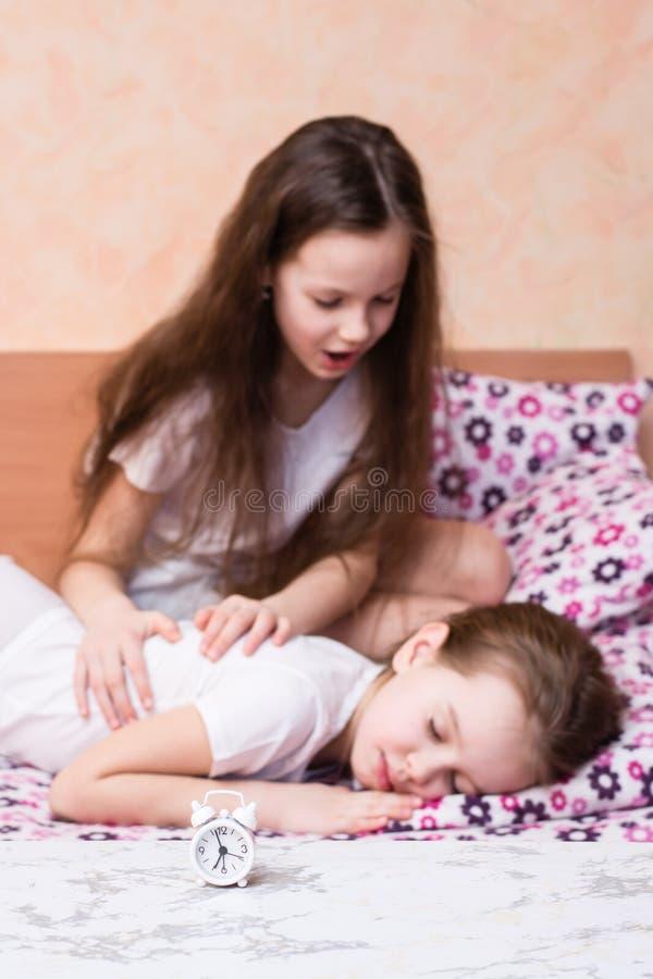 Biali budzików stojaki na stole na tle dziewczyna próbuje budzić się innej dziewczyny obraz royalty free