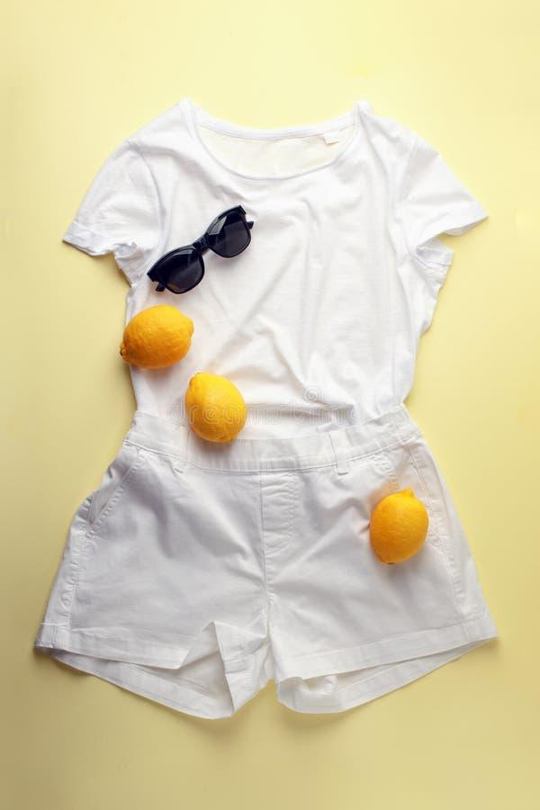 Biali cajgi, biała koszula, okulary przeciwsłoneczni i cytryny na żółtym tle, Kobiety wiosny lata elegancki strój Modny odziewa m zdjęcia royalty free