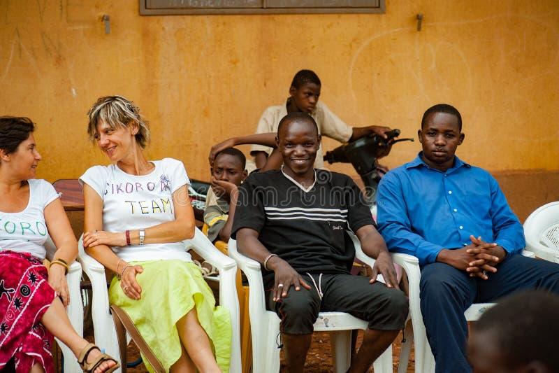 Biali caucasian ludzie i czarnych afrykanów ludzie cieszą się życie w wiosce zdjęcie stock