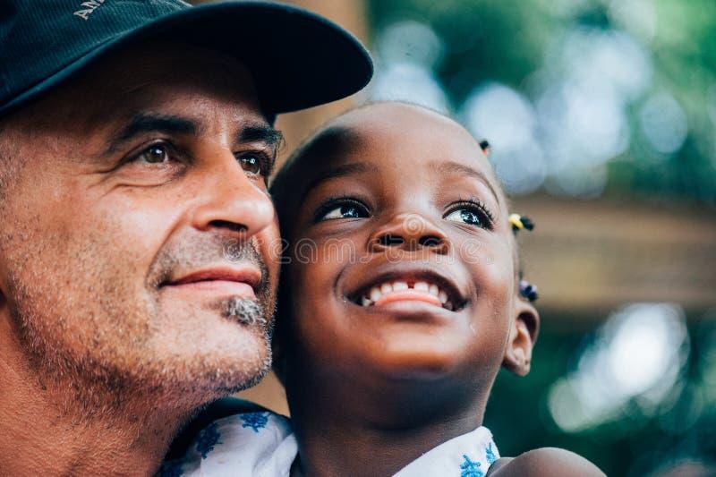 Biali caucasian ludzie i czarnych afrykanów ludzie cieszą się życie w wiosce zdjęcia stock