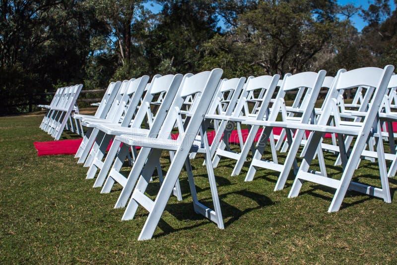 Biali ceremonii krzesła tworzyli outdoors z czerwony chodnik nawą na zielonej trawie zdjęcie royalty free