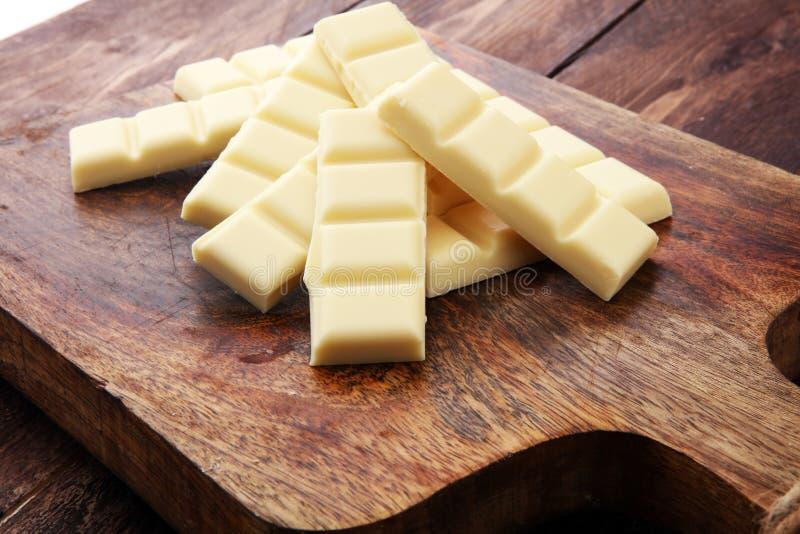 Biali czekoladowi bary i biali choco kawałki na drewnie obraz royalty free