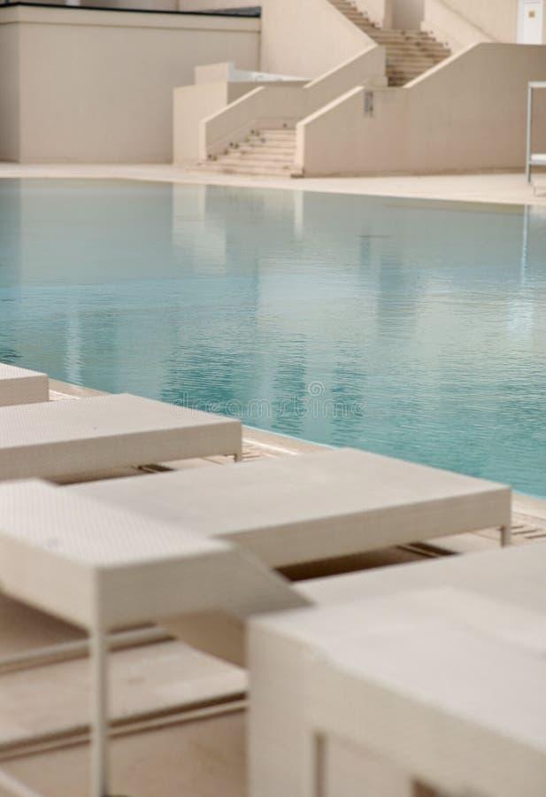 Biali deckchairs obok pływackiego basenu z krystaliczną błękitne wody i loungers fotografia stock