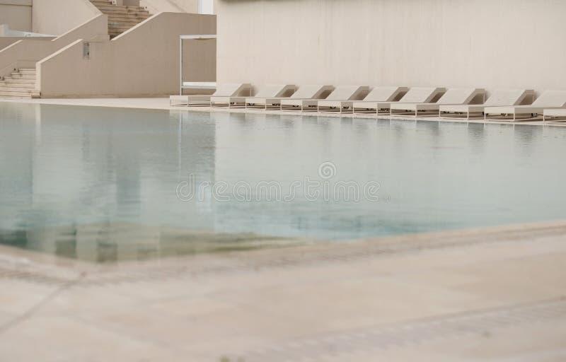 Biali deckchairs obok pływackiego basenu z krystaliczną błękitne wody i loungers zdjęcia royalty free