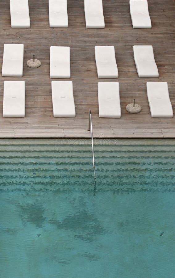 Biali deckchairs obok pływackiego basenu z krystaliczną błękitne wody i loungers fotografia royalty free