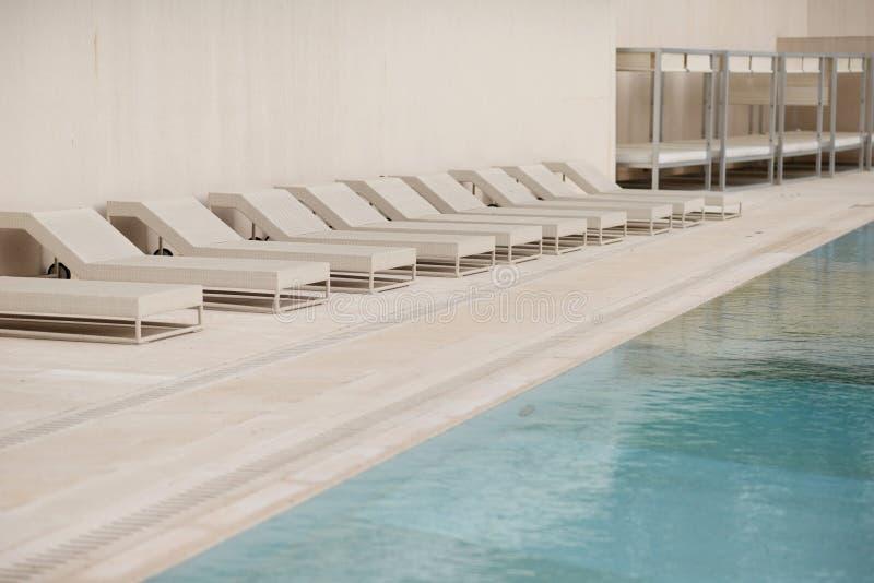 Biali deckchairs obok pływackiego basenu z krystaliczną błękitne wody i loungers obraz stock