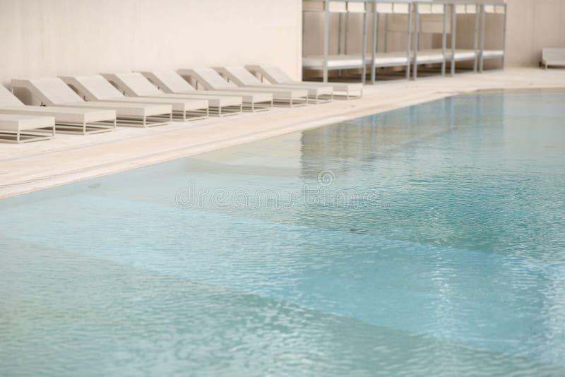Biali deckchairs obok pływackiego basenu z krystaliczną błękitne wody i loungers zdjęcie stock