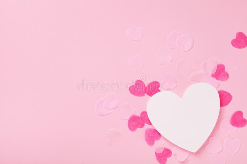 Biali drewniani kierowi i papierowi serca na różowego pastelowego tła odgórnym widoku Kartka z pozdrowieniami dla walentynek, kob fotografia stock