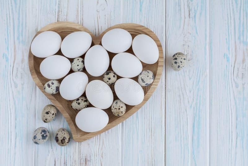 Biali jajka i przepiórek jajka w drewnianym sercu kształtowali talerza na drewnianym białym tle obrazy royalty free