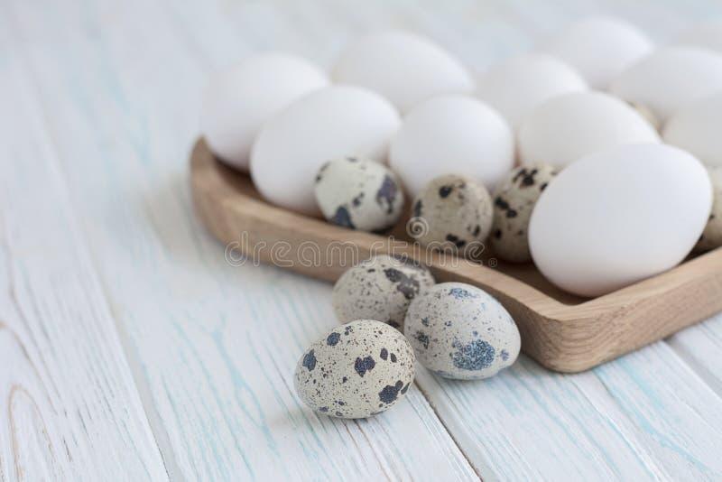 Biali jajka i przepiórek jajka w drewnianym sercu kształtowali talerza na drewnianym białym tle zdjęcie stock