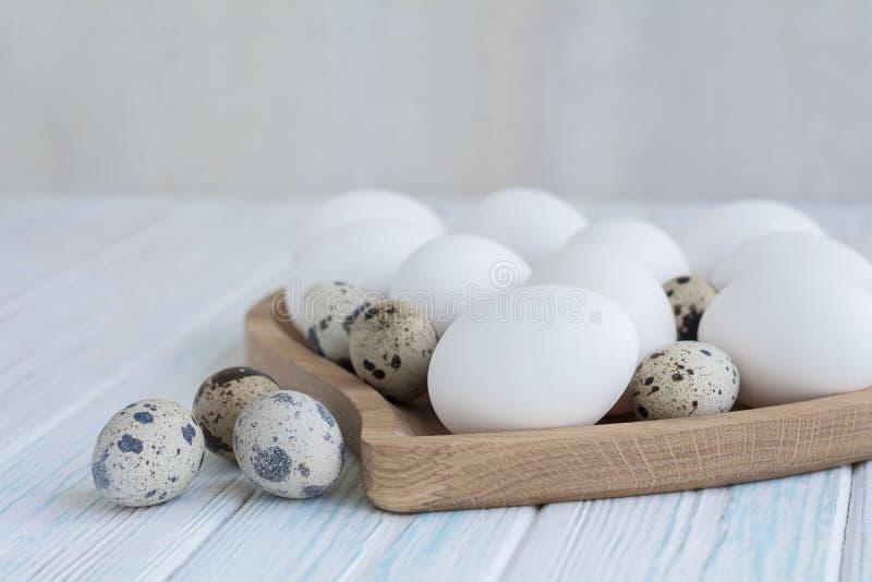 Biali jajka i przepiórek jajka w drewnianym sercu kształtowali talerza na drewnianym białym tle, Easter pojęcie obrazy stock