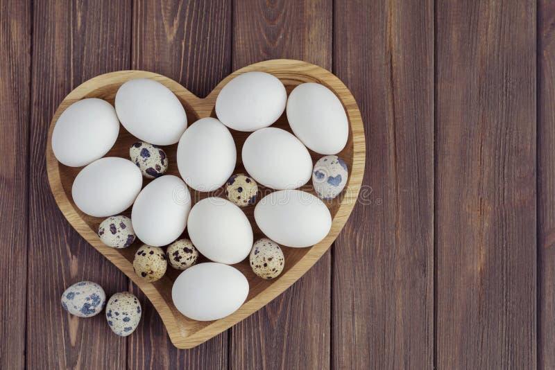 Biali jajka i przepiórek jajka w drewnianym sercu kształtowali talerza na drewnianym brown tle zdjęcia royalty free