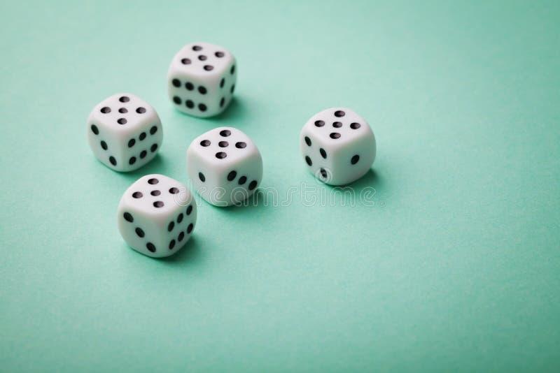 Biali kostka do gry na zielonym tle Uprawiać hazard przyrząda Odbitkowa przestrzeń dla teksta Wszystko liczą pięć Gra szansy poję fotografia stock