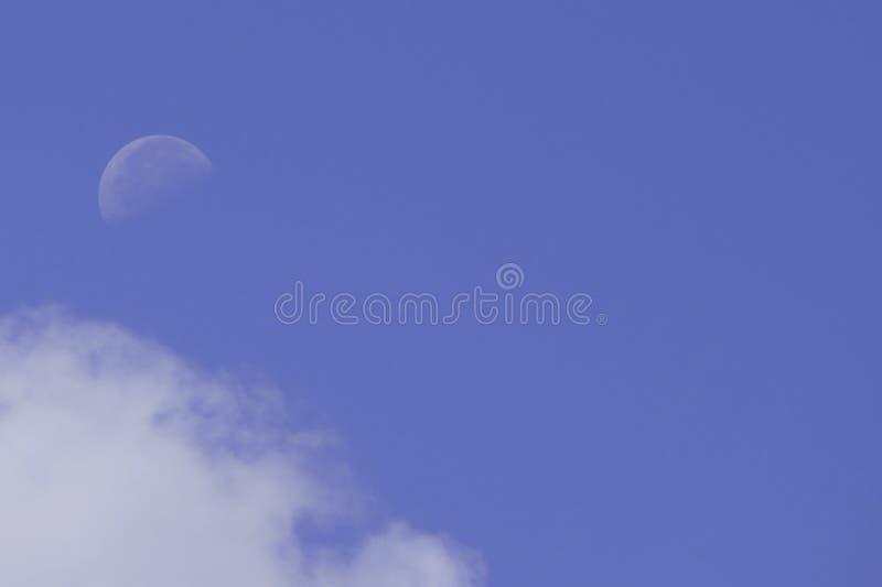 Biali księżyc, chmury i niebieskie niebo, obraz stock