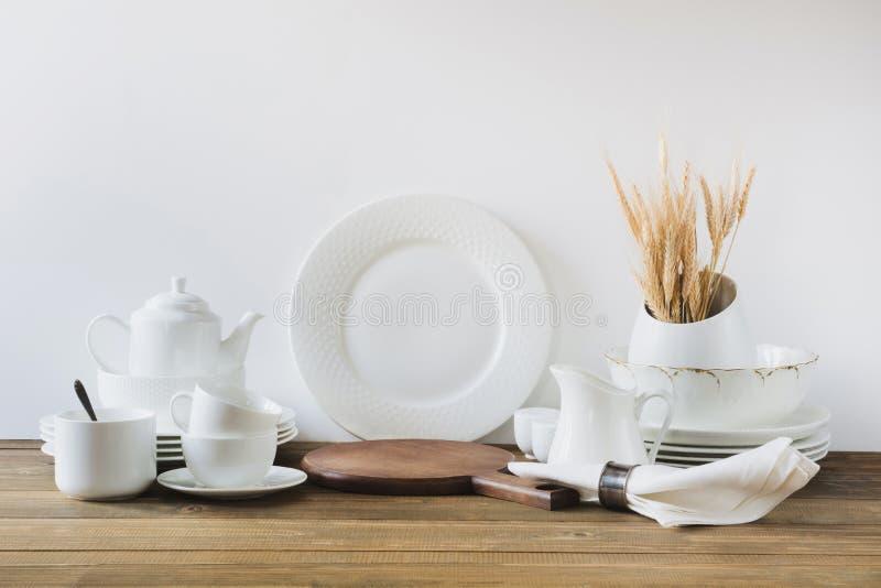 Biali kuchenni naczynia, dishware i inny różny biały materiał dla słuzyć na białej drewnianej desce, zdjęcia royalty free