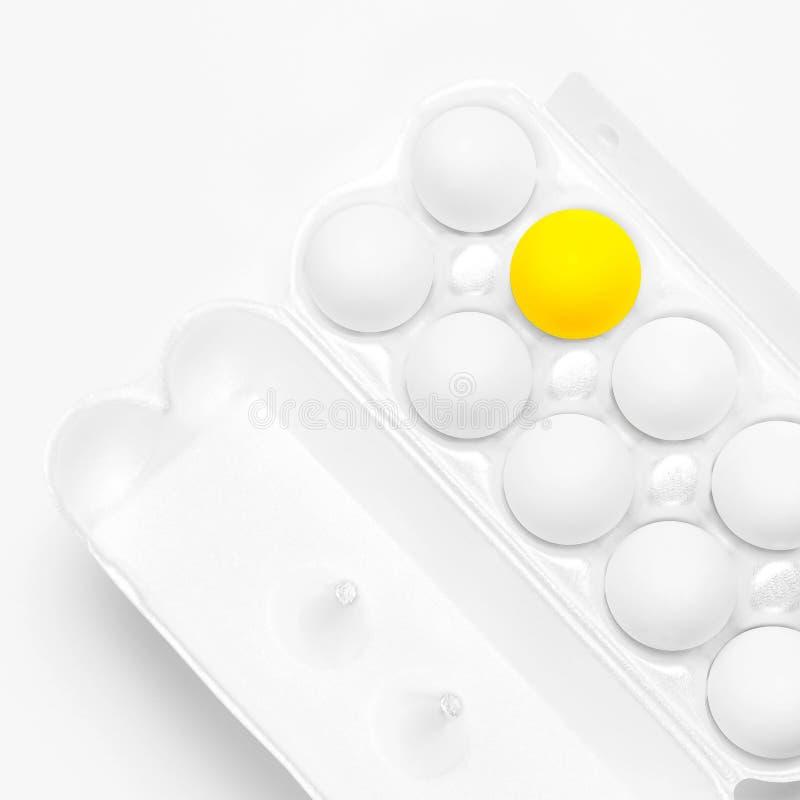 Biali kurczaków jajka i jeden żółty jajko w biały pakować na lekkim tło odgórnego widoku mieszkaniu nieatutowym Jajka w pudełku,  obrazy stock
