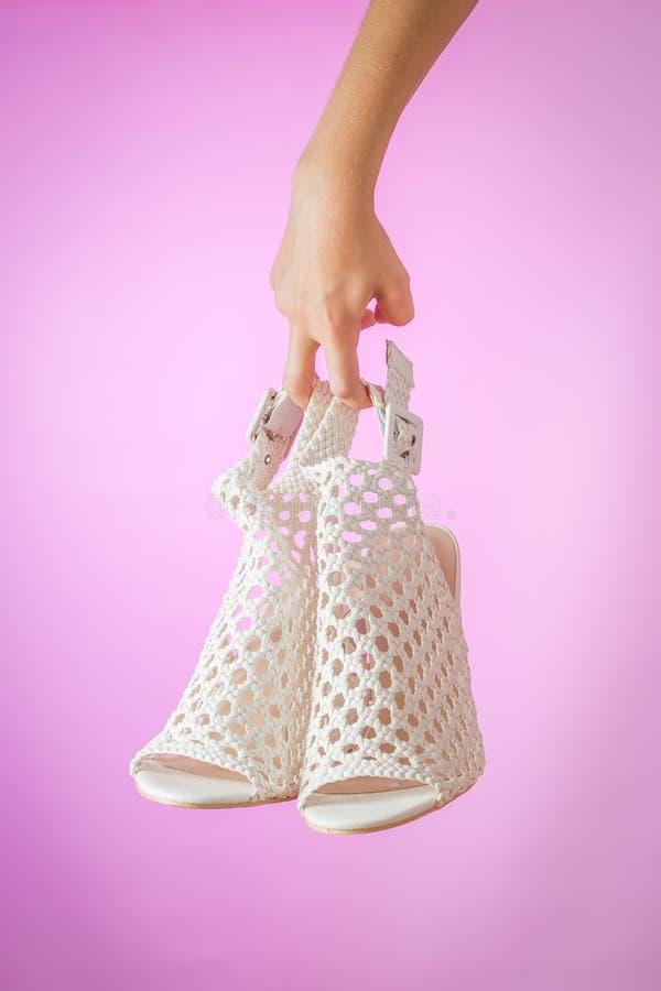 Biali mod kobiet lata buty w ręce na purpurowym tle obrazy royalty free