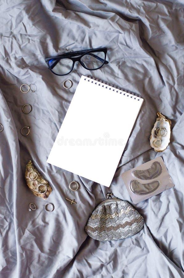 biali notepad i kobiet akcesoria na szarej tkaninie obraz stock