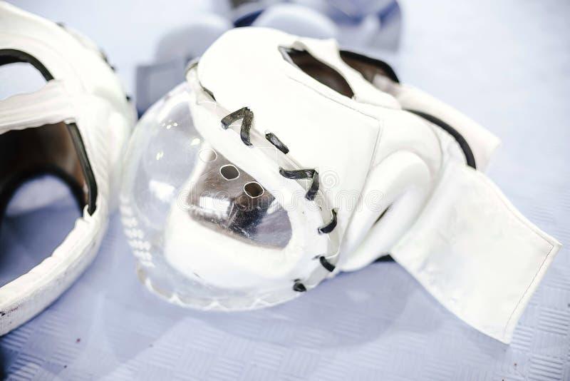 Biali ochronni hełmy z maską dla sztuka samoobrony na podłodze obraz royalty free