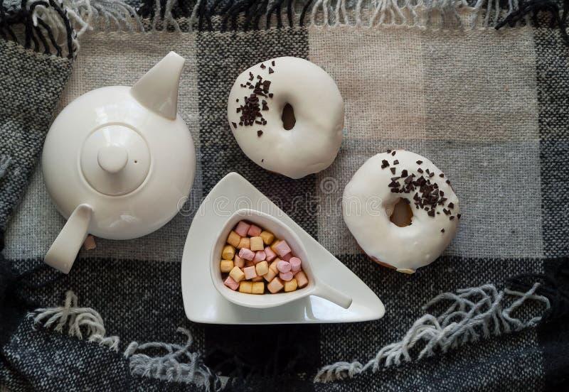 Biali oszkleni donuts i barwiony marshmallow w filiżance gorąca czekolada na szkockiej kracie w skandynawie projektują Mieszkanie fotografia stock