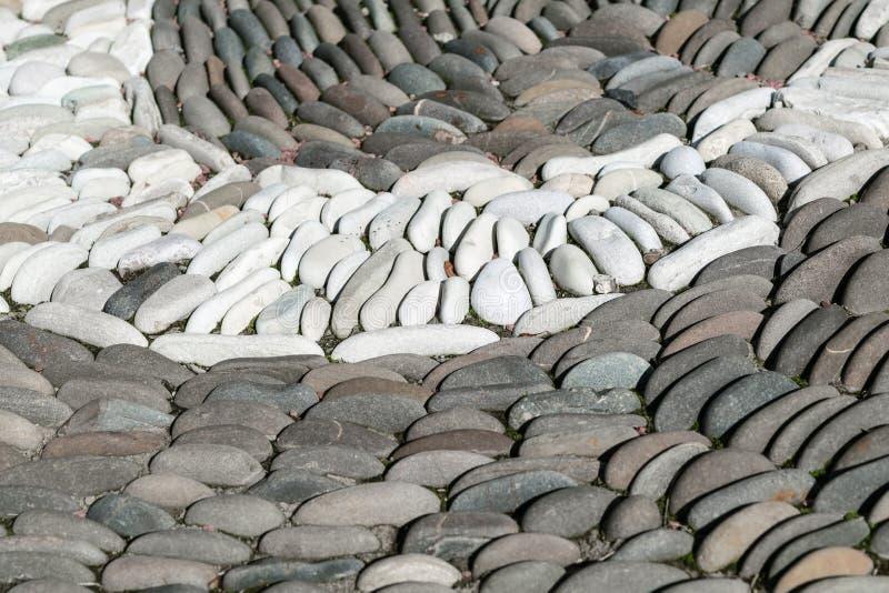 Biali owalni kamienie brogujący okrąg wśród ciemnych kamieni lub łuk obrazy royalty free