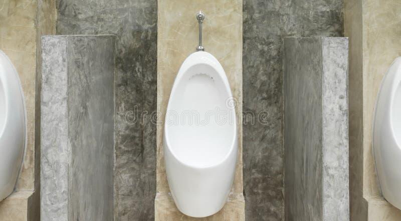Biali pisuarów mężczyzna w mężczyzna Jawnej toalecie z betonowej ściany Loft stylem fotografia royalty free