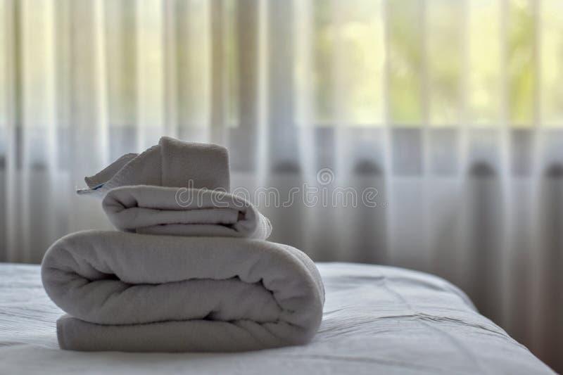 Biali ręczniki na łóżku zasłony jako tło fotografia royalty free