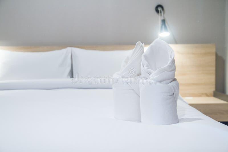 Biali ręczniki na wygodnym łóżku z wygodną sypialnią zdjęcie royalty free