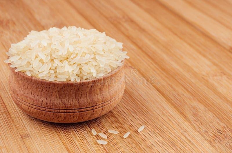 Biali ryż basmati w drewnianym pucharze na brown bambus desce, zbliżenie Zdrowy żywienioniowy zboża tło zdjęcie stock