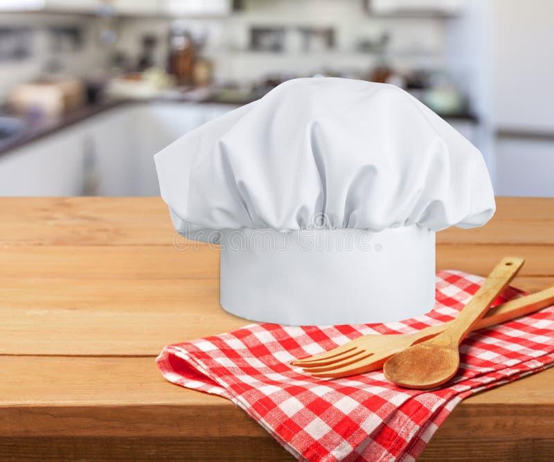 Biali szefów kuchni naczynia na stole i kapelusz obrazy stock