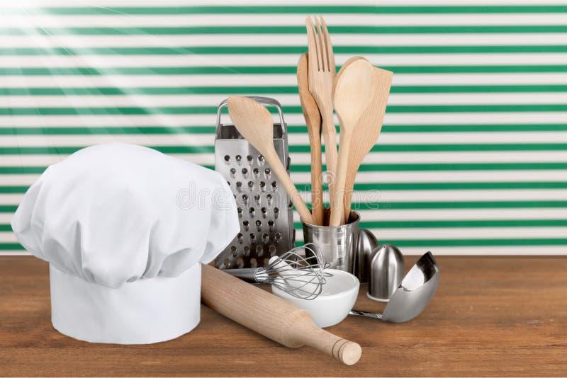 Biali szefów kuchni naczynia na stole i kapelusz zdjęcie stock