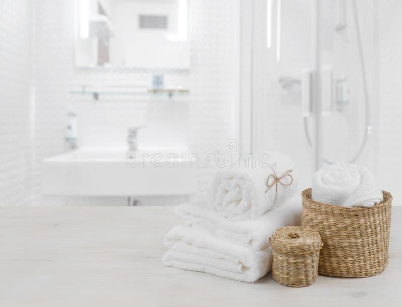 Biali zdrojów ręczniki i łozinowi kosze na defocused łazienki wnętrzu obraz royalty free