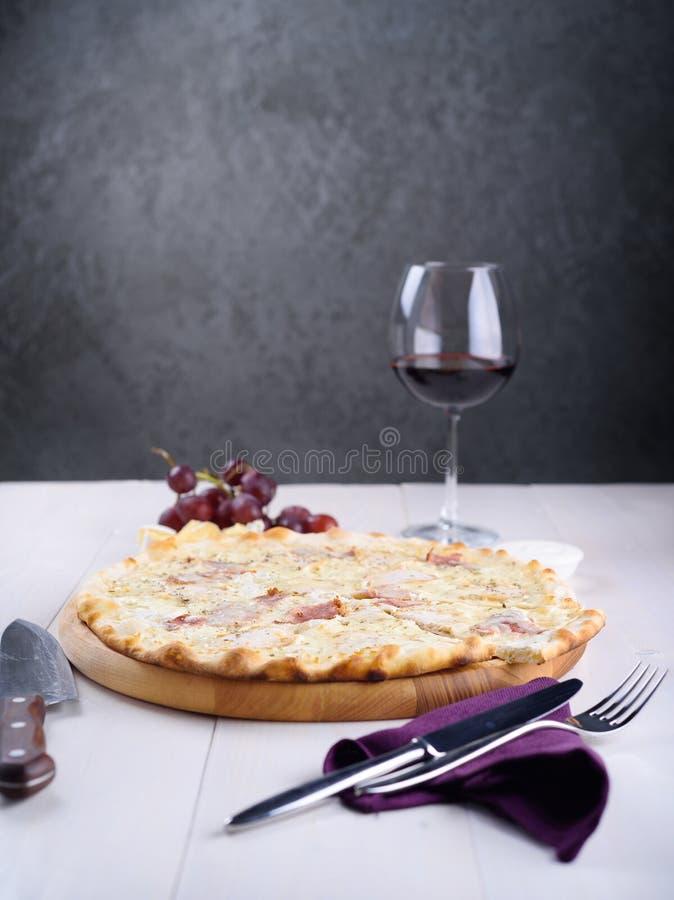 Bianca da pizza com galinha, presunto e molho de creme na placa de madeira ao lado de um vidro do vinho, das uvas e das partes de foto de stock