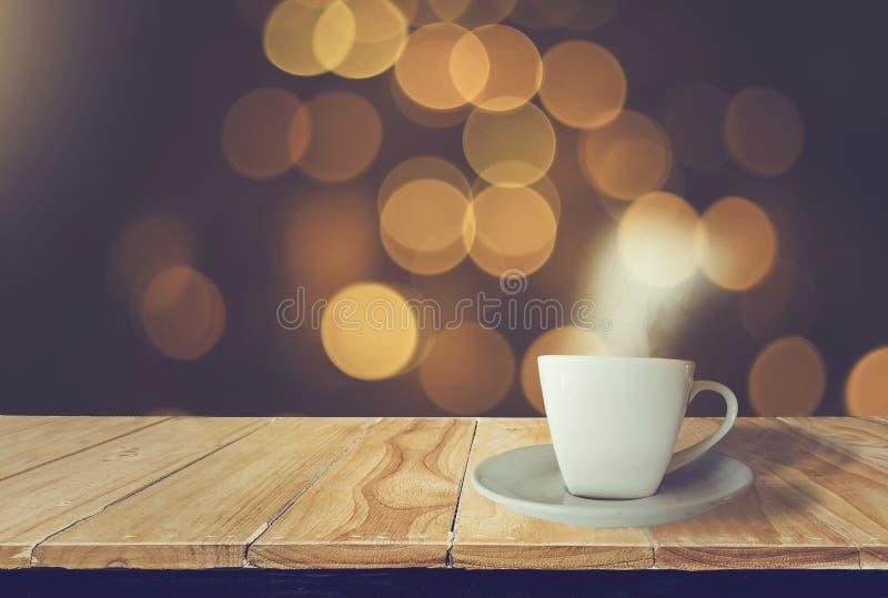 Bianco della tazza di caffè disposto sulla tavola di legno con fumo con il fondo di notte, bokeh dorato luminoso, brillante con i fotografia stock