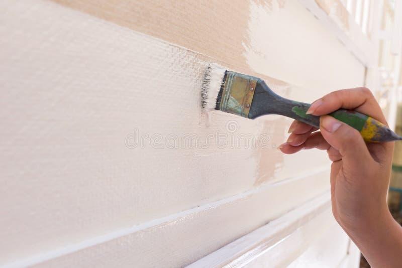 Bianco di verniciatura della spazzola della tenuta del lavoratore della mano immagini stock libere da diritti