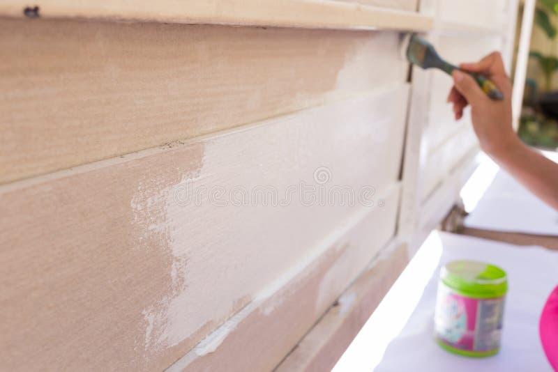 Bianco di verniciatura della spazzola della tenuta del lavoratore della mano fotografia stock