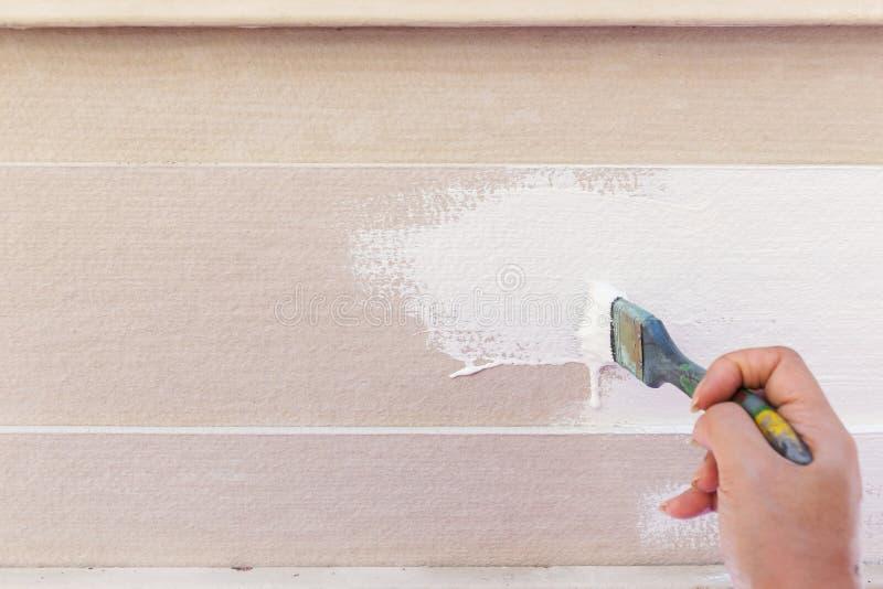 Bianco di verniciatura della spazzola della tenuta del lavoratore della mano fotografie stock