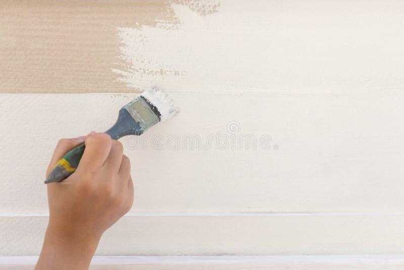 Bianco di verniciatura della spazzola della tenuta del lavoratore della mano fotografia stock libera da diritti