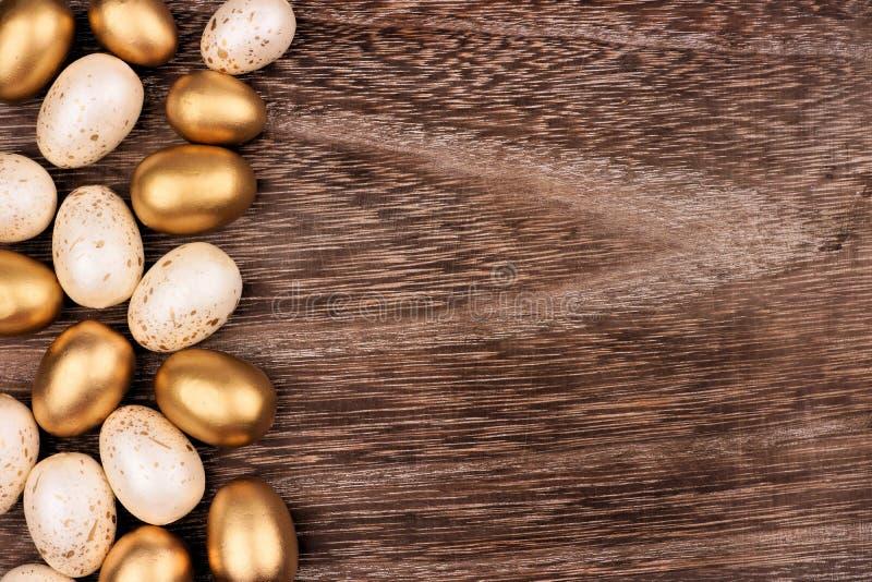 Bianco e confine del lato dell'uovo di Pasqua dell'oro sopra legno rustico fotografia stock